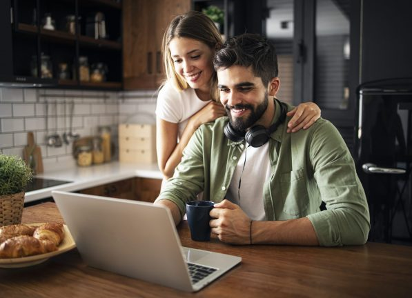 Portrait of a happy young couple smiling in the morning, using laptop in a modern kitchen